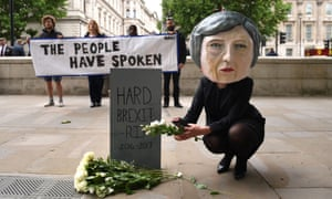A life-size giant-headed puppet of Theresa May leaving flowers at a tombstone bearing the words Hard Brexit RIP.