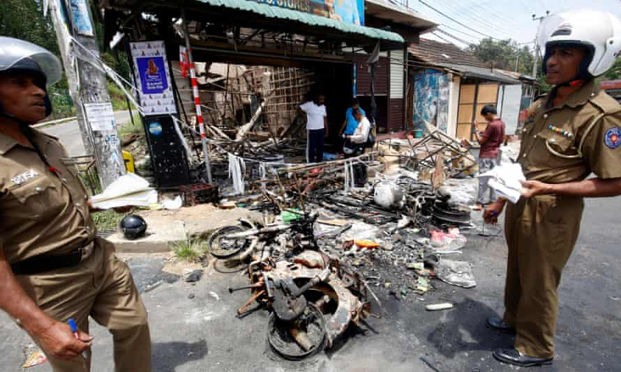 Sri Lankan policemen examine the remains of a business in Digana, Sri Lanka, after violence against Muslims last month.