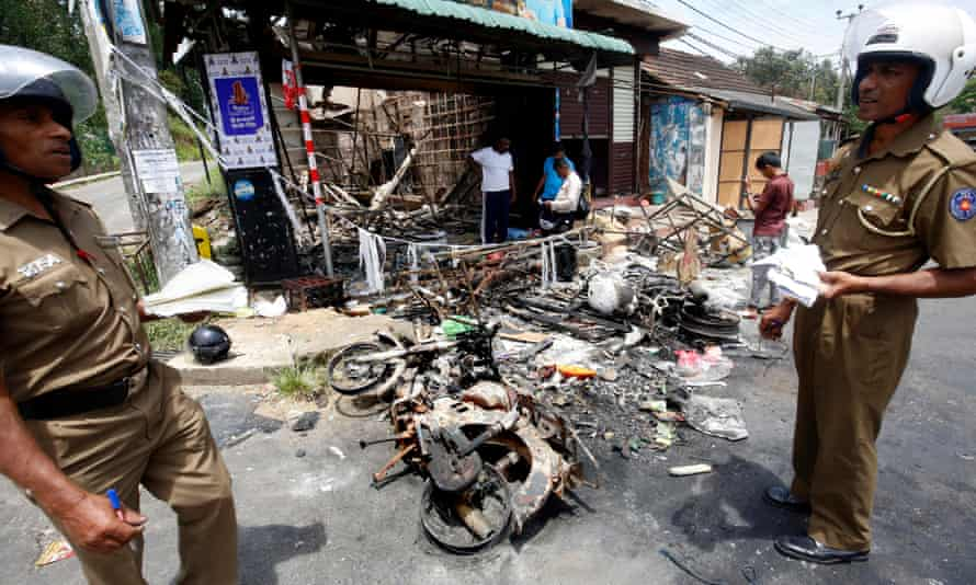 Sri Lankan policemen outside the gutted remains of a business in a riot-torn district in Kandy