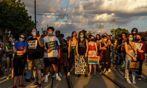 Protesters stand on a road during a march against the shooting of Jacob Blake in Kenosha, Wisconsin, on 27 August.