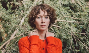 Miranda July in front of some bushes in an orange jumper