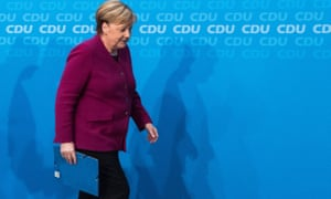 Angela Merkel leaves at the end of a press conference at the CDU headquarters after announcing she will not stand for re-election as chancellor.