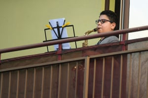 A boy plays the saxophone from a balcony during a flash mob to raise morale