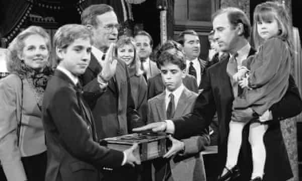 Joe Biden takes a re-enacted oath of office from Vice-President George Bush with his family in 1985.