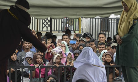 People watch as Tjia Nyuk Hwa is publicly flogged outside a mosque in Banda Aceh
