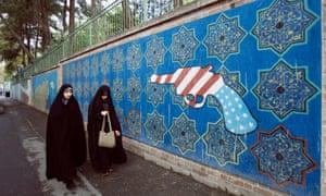Iranian women walk past a mural outside the former US embassy in Tehran.