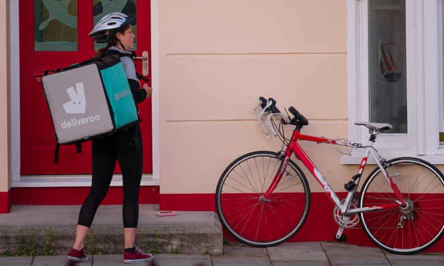 A young self-employed woman girl with her bicycle working for Deliveroo