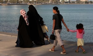 A housemaid accompanies two Qatari women with their children in Doha's Corniche