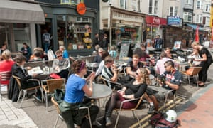 Holidaymakers enjoy the sunshine,outside cafes and shops