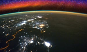 Bright swaths of red in the upper atmosphere, known as airglow, seen from the International Space Station.