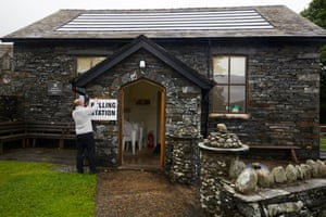 A clerk reattaches signs after they blew away in high winds at Lowick Community Hall in the Westmorland and Lonsdale constituency in Cumbria.
