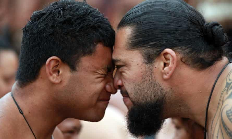 Waka Ama crew members welcome each other with a hongi (nose press) on the beach as they celebrate Waitangi Day on February 6, 2014 in Paihia, New Zealand.