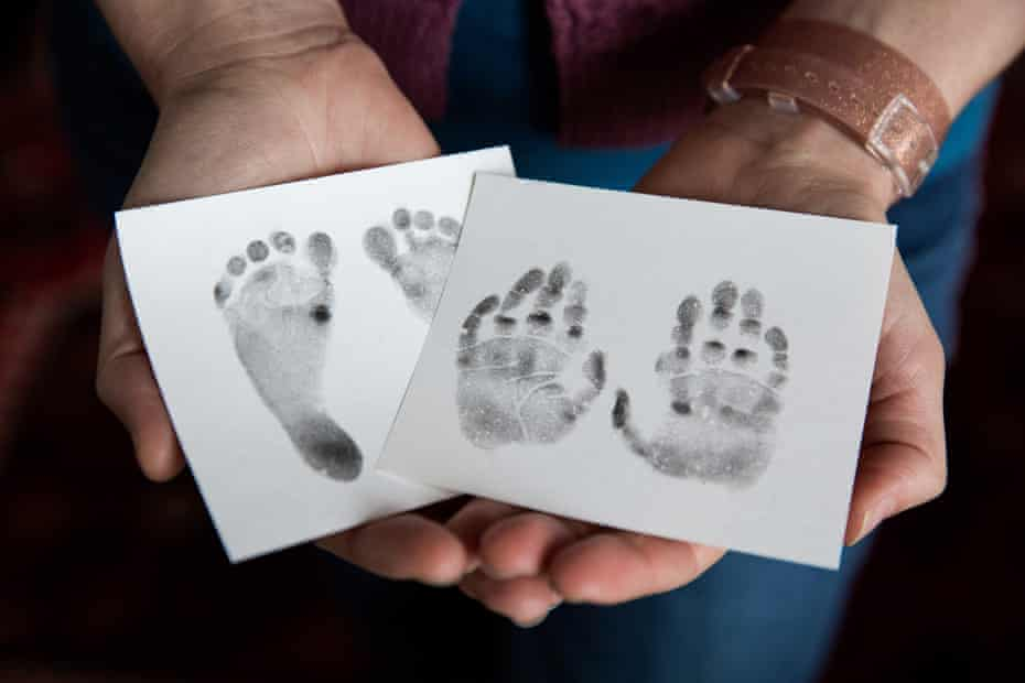 Kateholds her baby Laurel's foot and hand prints that were made by nurses at the clinic.