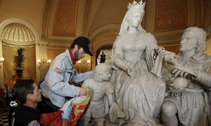 A demonstrator is removed from the statue of Queen Isabella and Christopher Columbus in the rotunda of the capitol in Sacramento, California, in 2018.