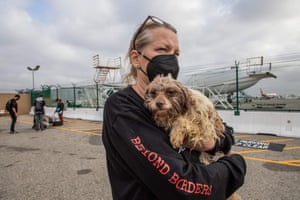 """Los Angeles, USA volunteer holds a rescued dog after 29 dogs arrived at Los Angeles International Airport in California. The dogs were rescued from the Yulin Dog Meat Festival in China and Chinese dog meat markets by """"No Dogs Left Behind,"""" a global animal welfare organisation. The dogs are on their way to forever homes in New York"""