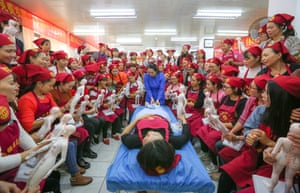 A teacher gives a demonstration of traditional Chinese medicine to students at a training centre in Haikou, China