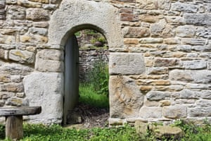 Classic bastle doorway of megalithic stone cut into a semicircular arch.
