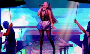 Ariana Grande performing in California last year, people with umbrellas on either side of her