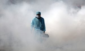 A worker sprays disinfectant in a deserted market in Jammu, India.