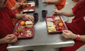 Detainees eat lunch at the Adelanto facility in 2013. Critics fear the private prison company Geo is manipulating local officials.