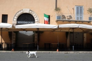 A dog passes by a closed restaurant in Rome on Tuesday