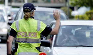 A police officer stops a driver at a checkpoint at Coolangatta