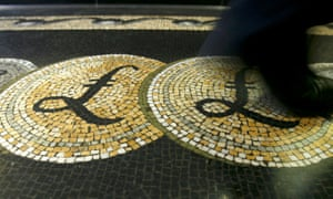 shows an employee walking over a mosaic depicting pound sterling symbols on the floor of the front hall of the Bank of England in London.