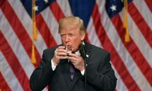Donald Trump takes a drink of water as he speaks about his administration's National Security Strategy at the Ronald Reagan Building and International Trade Center in Washington, DC