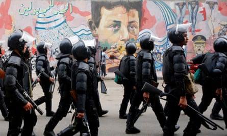 Riot police walk in front of graffiti, Cairo.