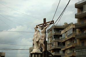 A crucifix and a statue of the Virgin Mary are seen on the roof of a shop in Jdeideh, northeast of Beirut.
