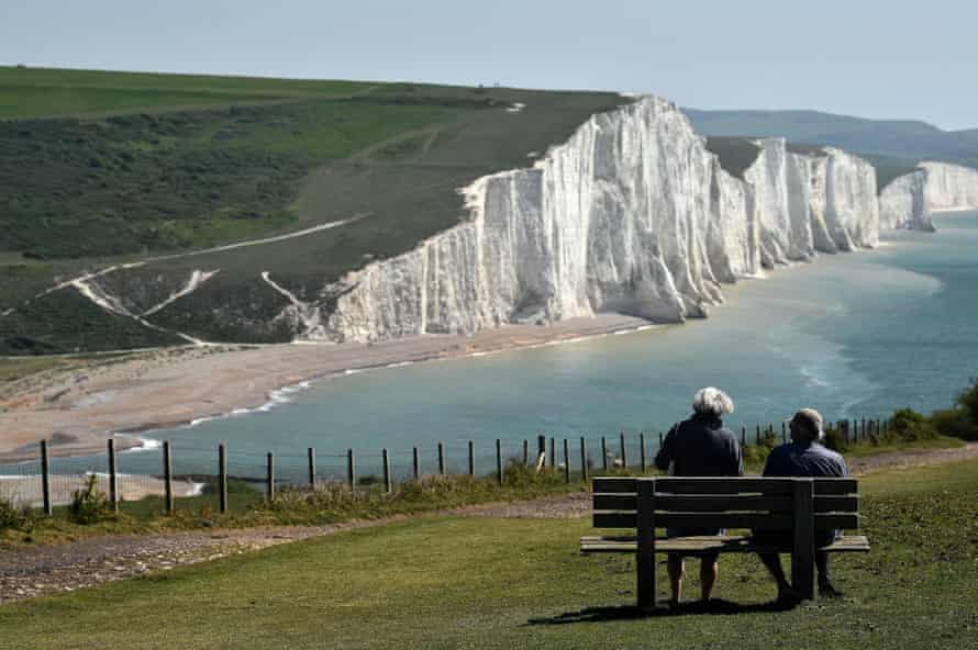 A couple sit on a bench overlooking the Seven Sisters cliffs near Eastbourne.