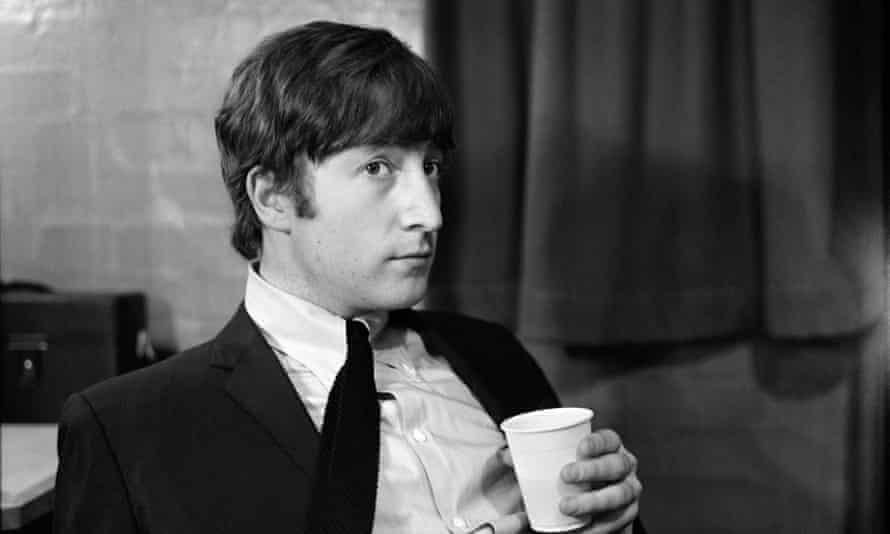 Black and white photo of Lennonin a suit,  holding a plastic cup,1963