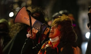 A protester with a loudhailer on a march through the streets of Seattle in remembrance of Breonna Taylor.