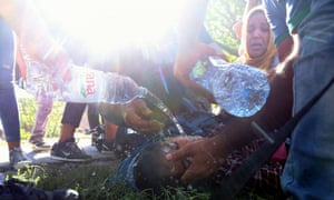 A woman faints after scuffles broke out with police who formed a cordon directing migrants and refugees towarsd waiting buses at the train station in the city of Tovarnik, close to the Croatian-Serbian border.