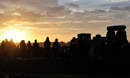 People gather to watch the sunrise on the longest day of the year during the summer solstice at the Stonehenge in Wiltshire, Britain, 21 June 2016.