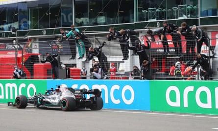 Pembalap Mercedes Lewis Hamilton melewati garis finis saat timnya melakukan selebrasi di sisi lintasan