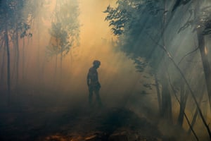 A firefighter surrounded by smoke and smog in Belem