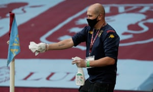A member of the Villa ground staff disinfects a corner flag at half time.