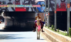 A man rides a horse down a deserted street in Allahabad