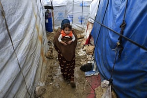A Syrian refugee woman carries her baby on her back as she walks in mud from the heavy rain, at a refugee camp in the town of Hosh Hareem, in the Bekaa valley, east Lebanon