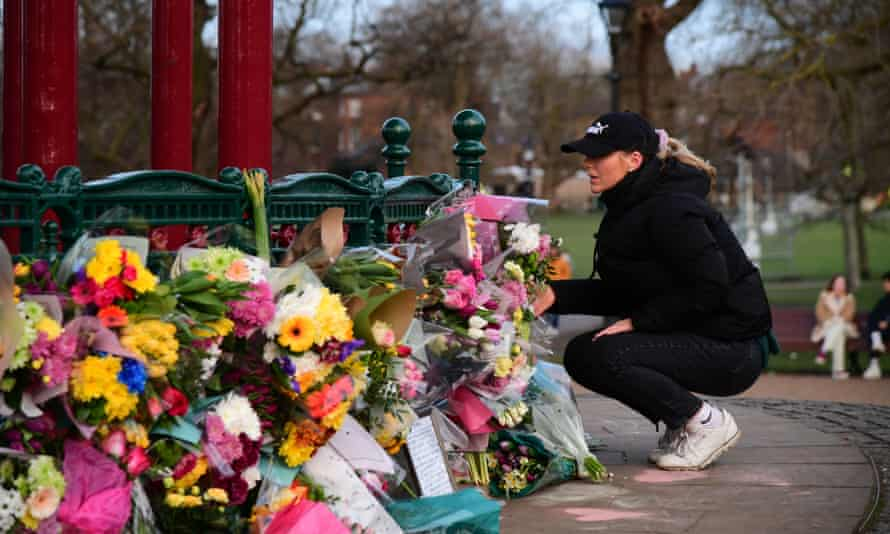 A woman leaves flowers at a memorial site for 33-year-old Sarah Everard in London Friday.