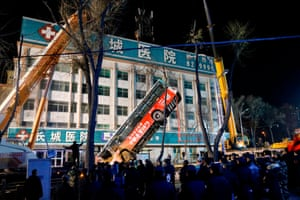 Xining, China: A bus is lifted after a sinkhole swallowed passersby and a public bus, killing six people and leaving 10 missing
