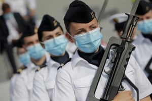 Paris, France Soldiers march in face masks prior to the Bastille Day parade on the Champs-Élysées. The usually grandiose military parade has been redesigned this year to celebrate heroes of the coronavirus pandemic