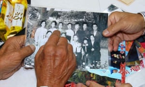 North Korean Sim Yeong-sik, 85, points to his family picture to show his South Korean relatives