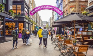 People walk along the Carnaby Street on the first day of stores reopening in April.
