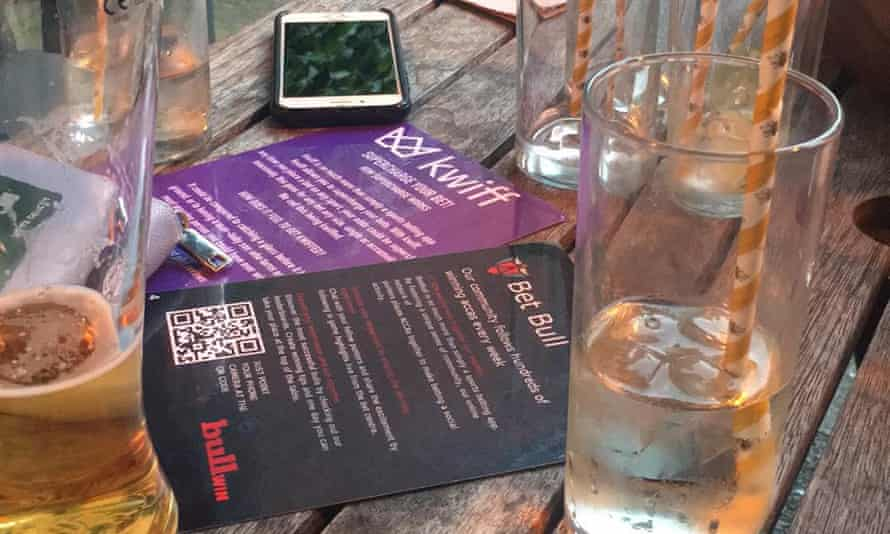 Kwiff and BetBull gambling flyers on a pub table with mobile phone and half empty glasses.