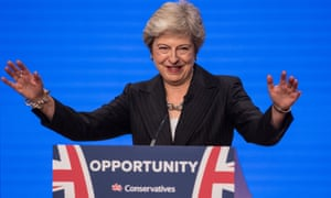 Theresa May, arms raised and smiling, from a  podium labelled 'Opportunity' at the 2018 Conservative party conference, Birmingham, UK.