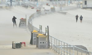 Joggers struggle against sand whipped up by strong winds at Bondi Beach in Sydney