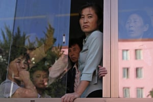 North Koreans look out from a bus on the streets of Pyongyang.