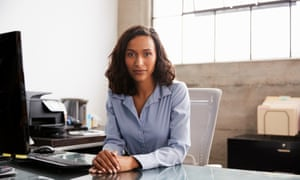Young woman at office desk looking to camera